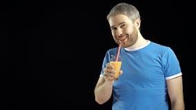 蓝色T恤杉的运动有胡子的年轻人喝与秸杆的橙汁 黑色背景 免版税库存照片
