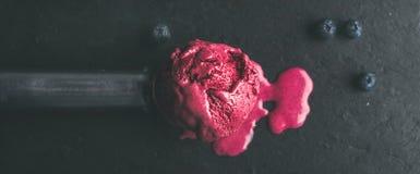 蓝莓冰淇凌熔化的瓢在黑板岩的向背景扔石头 免版税库存图片