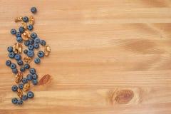 蓝莓和坚果在木背景 免版税库存照片