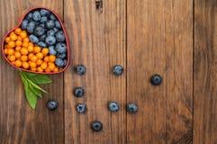 蓝莓和鼠李被计划以在木背景的心脏的形式 顶视图 特写镜头 库存图片