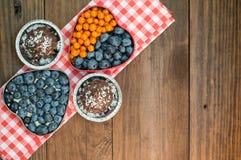 蓝莓和鼠李被计划以心脏块菌状巧克力的形式 木背景 顶视图 特写镜头 免版税库存照片