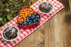 蓝莓和鼠李被计划以心脏块菌状巧克力的形式 木背景 顶视图 特写镜头 免版税库存图片