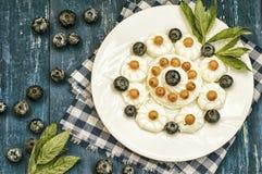蓝莓和鼠李被计划以心脏的形式用奶油色蛋白甜饼 木背景 顶视图 特写镜头 免版税库存图片