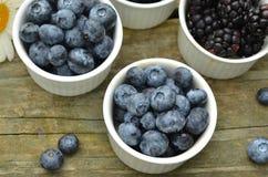 蓝莓和黑莓在土气木桌上的庭院雏菊 免版税库存图片