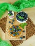 蓝莓在一个陶瓷碗,在一个三明治用花生酱和在酸奶 图库摄影