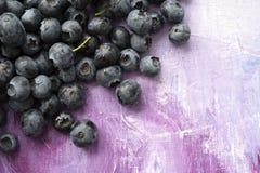 蓝莓新鲜的健康莓果在淡紫色抽象帆布的 免版税库存图片