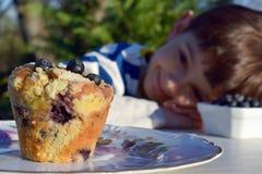 蓝莓松饼被弄脏的孩子在背景中 免版税图库摄影