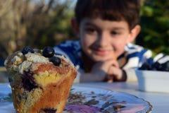 蓝莓松饼被弄脏的孩子在背景中 免版税库存图片