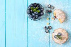 蓝莓松饼 自创被烘烤的杯形蛋糕用蓝莓,新鲜的莓果,薄菏,搽粉了在蓝色木背景的糖 顶视图 库存照片