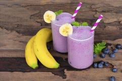 蓝莓汁和香蕉圆滑的人在玻璃饮料的一份鲜美健康饮料在木背景的早晨 库存照片