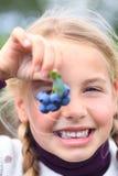 蓝莓注视前女孩她的藏品 免版税库存照片