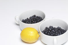 蓝莓涌入白色杯子和柠檬,切成了两半 在白色背景的谎言 库存图片
