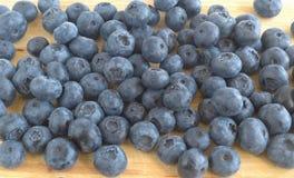 蓝莓莓果在切板驱散了 库存图片
