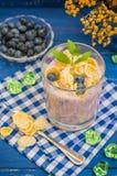 蓝莓酸奶、谷物和薄菏小树枝  木蓝色背景 顶视图 特写镜头 免版税图库摄影