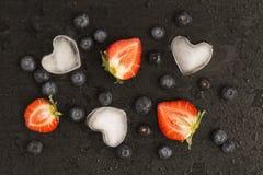蓝莓,在湿黑石背景的草莓 库存图片