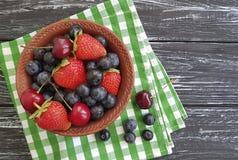 蓝莓,草莓在一个老黑木夏天编组土气樱桃有机生气勃勃毛巾抗氧剂 免版税库存图片