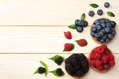 蓝莓,黑莓,在木碗的莓的混合在轻的木桌背景 库存照片
