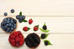 蓝莓,黑莓,在木碗的莓的混合在轻的木桌背景 免版税库存图片