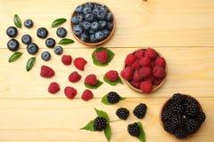 蓝莓,黑莓,在木碗的莓的混合在轻的木桌背景 库存图片