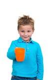 蓝蚝的三岁的男孩从杯子喝,隔绝在白色 库存照片