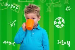 蓝蚝的三岁的男孩从杯子喝 库存图片