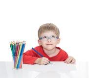 蓝蚝的五岁的男孩坐在一张白色桌上和并且画铅笔 免版税库存照片