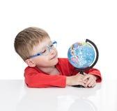 蓝蚝的五岁的男孩坐在一张白色桌上并且拿着地球手中 免版税图库摄影