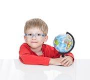 蓝蚝的五岁的男孩坐在一张白色桌上并且拿着地球 图库摄影