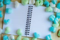 蓝绿色心脏和空白的笔记本 免版税库存图片