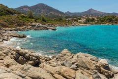 蓝绿色海和岩石在Cala d'Olivu在Ile鲁塞附近在惊叹 免版税库存照片