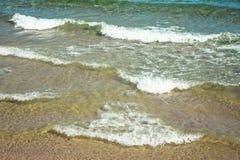 蓝绿色海和沙子的起伏式波在一个晴天靠岸 库存图片