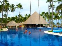 蓬塔Cana,多米尼加共和国- 2013年2月04日:休息在Barcelo Bavaro的普通的游人使有水池的旅馆靠岸 免版税库存照片