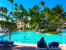 蓬塔Cana,多米尼加共和国- 2013年2月02日:休息在VIK竞技场有水池的布朗卡旅馆里的游人在棕榈下 免版税图库摄影