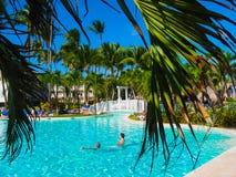 蓬塔Cana,多米尼加共和国- 2013年2月02日:休息在VIK竞技场有水池的布朗卡旅馆里的游人在棕榈下 免版税库存照片