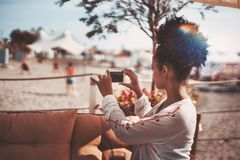 蓬松卷发在智能手机海滩体育的女孩射击 图库摄影