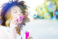 蓬松卷发妇女吹的肥皂泡 免版税图库摄影