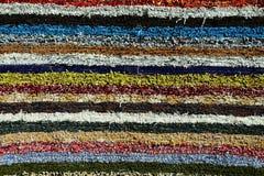 蓬松手工制造地毯纹理在手摇纺织机,各种各样的五颜六色的垂直线的样式生产了 免版税库存照片