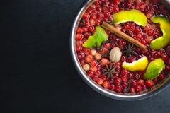 蔓越桔、桂香和果皮在一个嫩煎平底锅在一块黑石头 库存照片