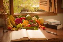 蔬菜、水果和书 图库摄影