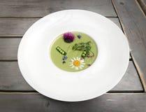 蔬菜汤捣碎了绿豆和硬花甘蓝,装饰用花和芬芳草本 享用盘 库存照片