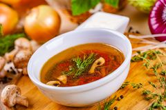 蔬菜汤用草本和香料在白色板材 图库摄影