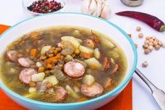 蔬菜汤用鸡豆和熏制的香肠 免版税库存照片