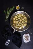 蔬菜菜肴,夏南瓜油煎了用在一个平底锅的迷迭香在黑暗的木背景 顶视图 免版税库存照片