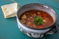 蔬菜通心粉汤汤供食与面包片 库存图片