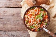 蔬菜通心粉汤汤和面包在桌上 水平的顶视图 库存照片
