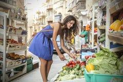 蔬菜水果商的一个女孩 免版税库存图片