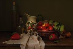 蕃茄、胡椒和炊具在桌上 库存照片