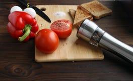 蕃茄、胡椒和鸡蛋在桌上 库存图片