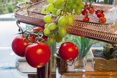 蕃茄、葡萄、臀部和金黄盘子在玻璃桌上 免版税库存照片