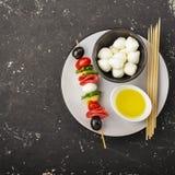 蕃茄、蒜味咸腊肠、无盐干酪、蓬蒿叶子和薄荷的意大利式饺子,在回合的maslik可口开胃菜串  图库摄影